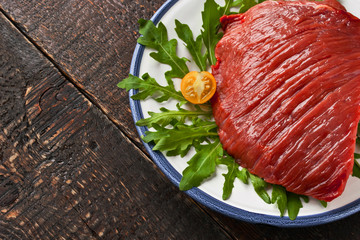 Raw red meat on the plate on the wooden table