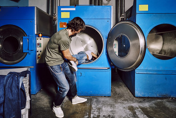 Young couple playing in an industrial laundry