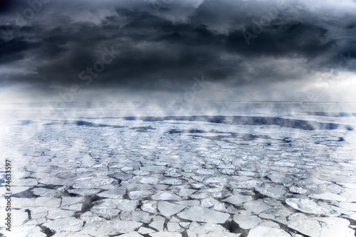 Winter seascape with dark clouds over frozen sea.