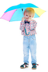 Little boy stands under a colorful umbrella.