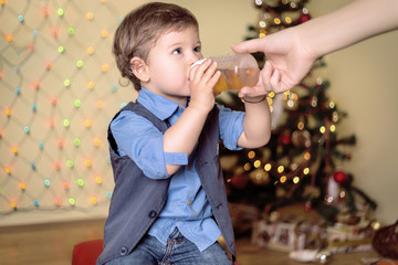 Mother gives a bottle to her son on a christmas eve