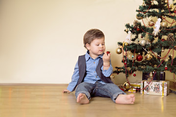 Boy looking at christmas ball in front of christmas tree