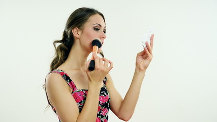 beautiful girl puts on makeup on a white background