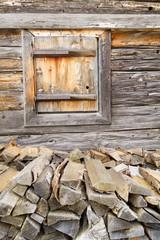 Brennholz an der Hauswand mit Fenster