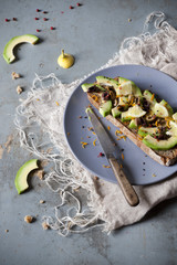 wholemeal vegan toast with avocado slices on plate with knife