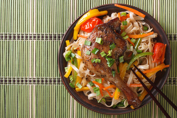 Roasted duck leg with rice noodles on a bamboo table  top view