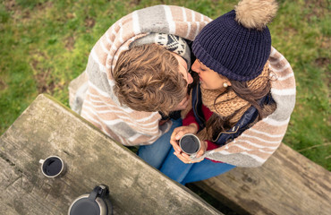 Young couple under blanket with hot drink kissing outdoors