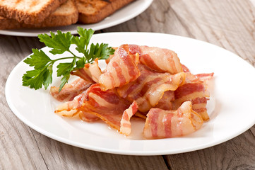 delicious hot fried bacon on a white plate and toast