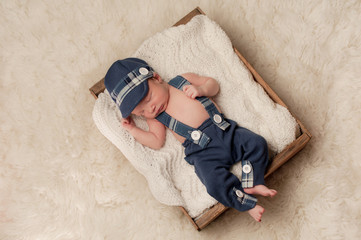 Newborn Baby Boy Wearing a Hat and Suspenders