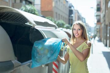 Woman with trash bags near garbage bin