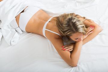 Woman wearing underwear posing on bed