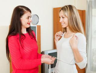 woman measuring  waist of happy girlfriend