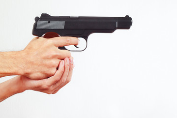 Hands with semi-automatic pistol on a white background