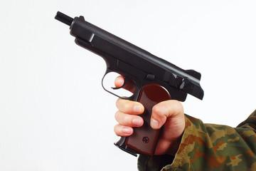 Hand in camouflage uniform with discharged gun