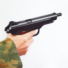Hand in camouflage uniform with discharged handgun