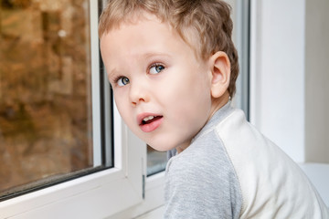 Cute kid at home by window