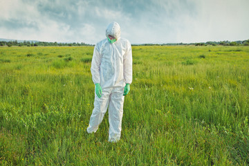 Scientist in biohazard uniform on summer field