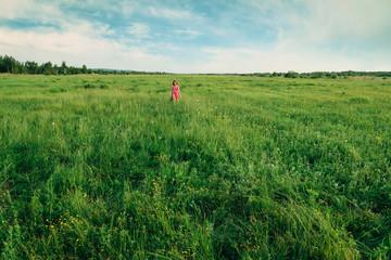 Happy little girl walking on summer meadow