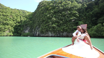 handsome groom hug his beautiful brunette bride sitting on boat