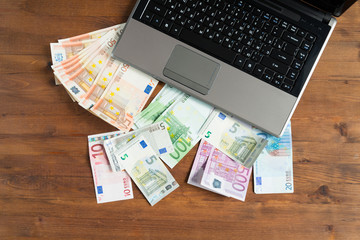 Pile of euro money with Laptop