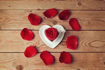 Rose flower petals and heart shape coffee cup on wooden table