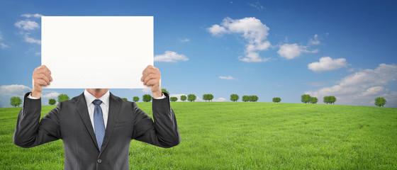 Mann mit Schild vor Landschaft