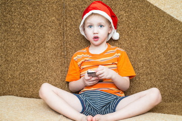 Boy using his smartphone while seated in front of the Christmas