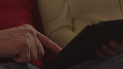 Elder couple using tablet - close up of hands