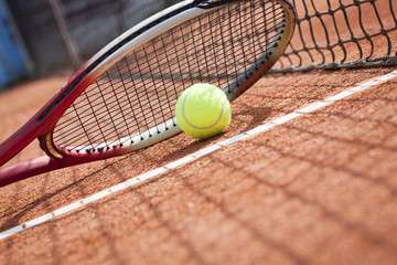 Close up of tennis racquet and ball on the clay tennis court