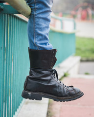 Detail of black boot in a city park
