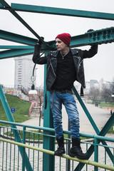 Punk guy standing on a bridge