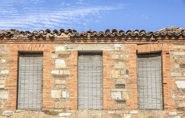 windows with shutters in an ancient brick house