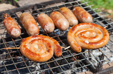 Tasty pork and beef sausages cooking over the hot coals on a bar