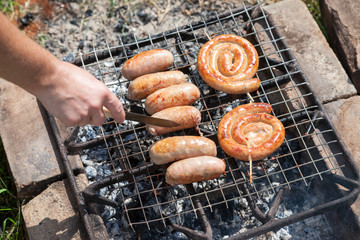 Fresh sausage and hot dogs grilling outdoors on a barbecue grill