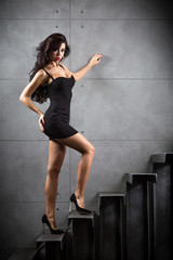 Sexy brunette woman sitting on stairs