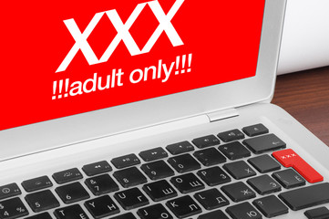 Online porn concept. XXX adults only message on silver laptop an