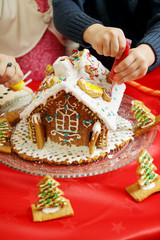 children decorate the gingerbread house