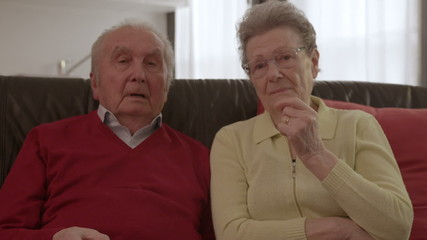 Elder couple watching TV, arguing and changing channels