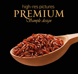 Red rice in a wooden spoon  isolated on black background