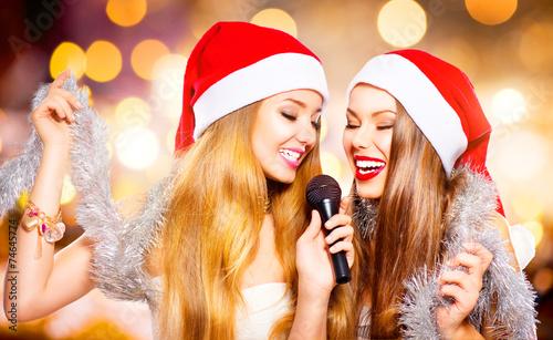 Christmas party, karaoke. Beauty girls in santa hats singing - 74645774