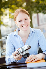 Smiling Woman with Camera and a Book