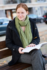 Young Woman Reading a Novel in a City