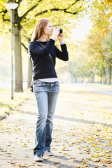 Young Woman with a Camera in a Park