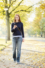 Woman Walking and Using a Mobile Phone