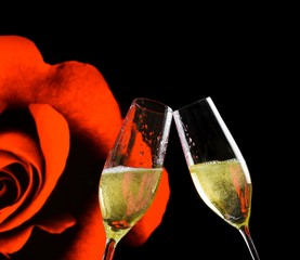 champagne flutes on rose flowers and black background
