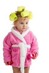 Little girl in a bathrobe and curlers