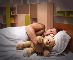 Sleeping man in bed with toy bear