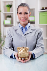 portrait of happy smiling business woman, holding gold piggy ban