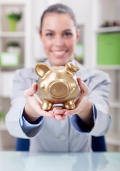 business woman holding gold piggy bank,focus on piggy bank