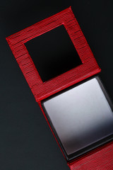 Red black rectangular ring box on dark background